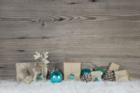 aquamarine: Christmas decoration of wood and paper in beige brown white and turquoise colors on wooden snowy background.