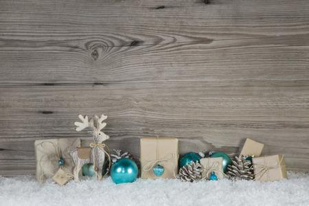 Décoration de Noël de bois et de papier dans les couleurs blanc et turquoise marron beige sur fond de neige en bois.
