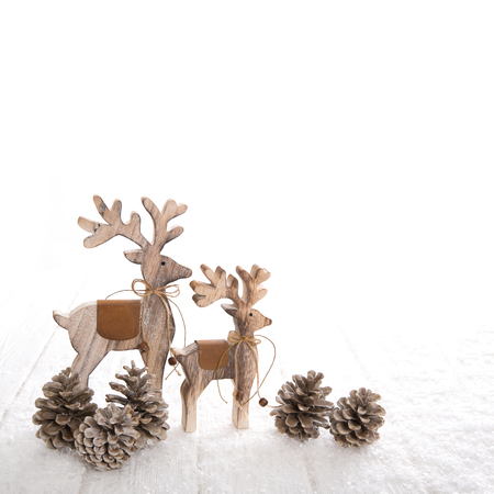 Couple of thw wooden deer with fir cone on white wooden background.