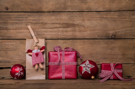 Christmas presents on wooden rustic background with angel and red white checked gifts wrapped in paper. Imagens