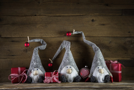 Three santa with red white checked christmas presents on wooden old background.