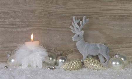 One burning advent candle with deer on wooden brown shabby background with snow.