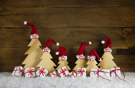 Red white christmas gift boxes with handcrafted trees on old wooden background for decoration.