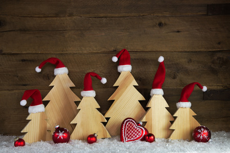 Romantic wooden christmas background with red santa hats and crafted trees with snow.