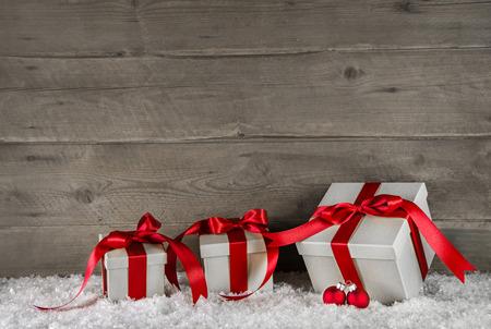 Red christmas présente sur fond brun de neige en bois.