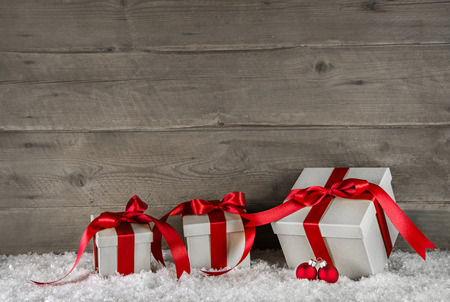 Red christmas presents on brown wooden snowy background.