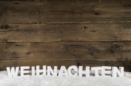 Old antique wooden background with white german letters for Christmas.