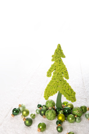 Isolated apple green christmas tree of wool decorated with balls over white background. Imagens