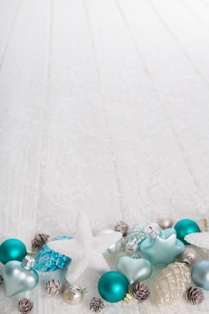 Light turquoise and blue wooden snowy white christmas background with balls, stars and hearts for decoration. Imagens