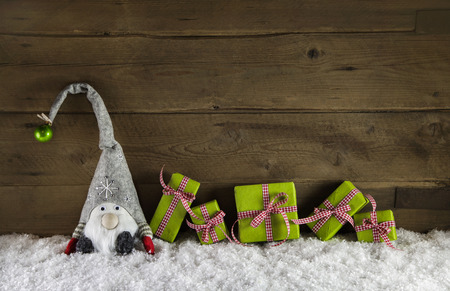 Rustic country style wooden christmas background with gift boxes in red and green colors with a santa in the snow.