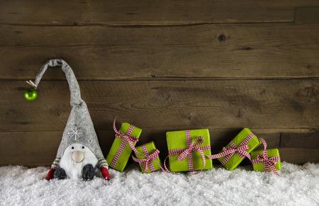 stile: Rustico stile country in legno sfondo di Natale con scatole da regalo nei colori rossi e verdi con una Santa nella neve.