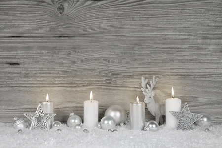 adviento: Shabby chic christmas background in grey, white and silver colors with for burning advent candles for luxurious decorations.
