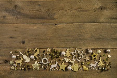 Brown wooden background with golden christmas decoration of miniatures.
