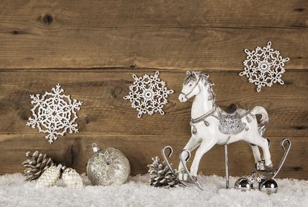 fond brun en bois avec un cheval à bascule sur fond de neige pour les décorations de Noël.