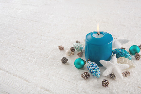 One burning advent candle in turquoise, blue, brown and white colors for christmas decoration.