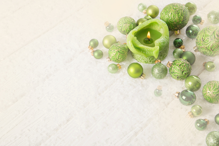 Green and white xmas  background with snow, candle and balls for decoration items.