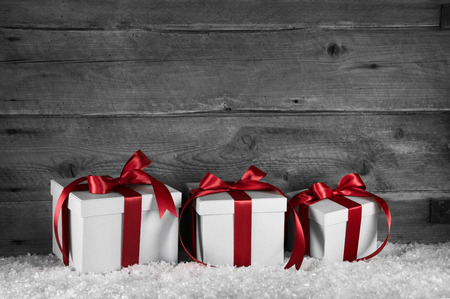 Three red white christmas presents on old wooden grey background.