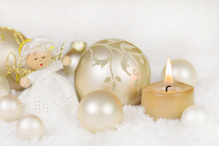 Christmas decoration with one burning candle, angel and balls in golden colors with snow.