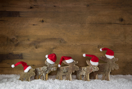 santa moose: Old wooden background. Christmas decoration in red white and a group of santa in the snow. Stock Photo