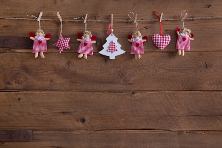 Handmade country style christmas decoration with angels, star and red white checked hearts on rustic old background. Imagens