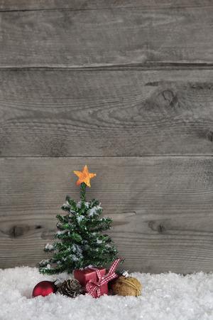 Bois vieux fond de campagne avec un arbre de Noël vert et une boîte-cadeau rouge avec ruban vérifié. Banque d'images