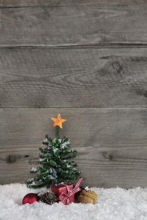 Wooden old country background with a green christmas tree and a red gift box with checked ribbon. Imagens