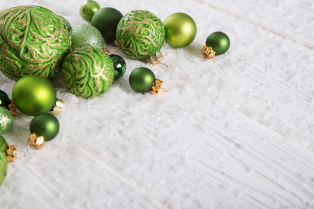 Green and white xmas background with snow and balls for decoration items.