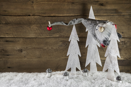 Humorously christmas background of wood with snow and a santa hanging in a tree. Imagens