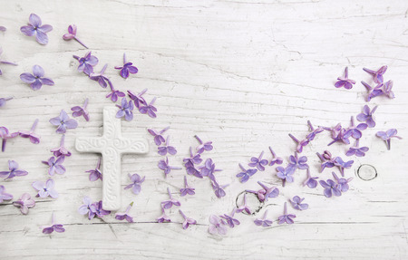 Cross and violet or purple lilac blossom on old wooden shabby background for a condolence card. Stock Photo