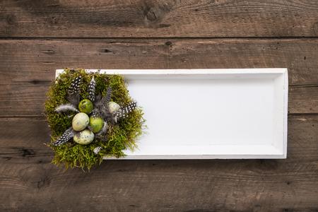 nid de Pâques à la main sur le panneau en bois ou un cadre en brun naturel, les couleurs vertes et blanches sur fond vieux bois.