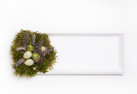 Handmade Easter nest on wooden sign or frame in natural brown, green and white colors on wooden old background. Imagens