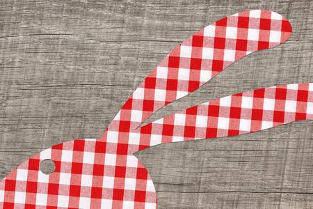 easter background en bois avec un rouge vérifié lapin pour une carte de voeux.