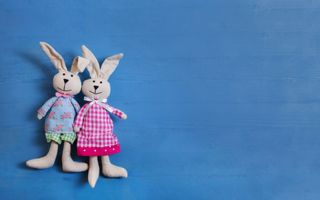 Cute couple of handmade sewed easter bunny on blue wooden background for decoration items.
