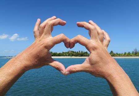 Mains faisant coeur. concept de vacances Tropical avec de l'eau bleue et le ciel et une plage de sable blanc avec des palmiers dans le dos.