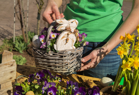 Easter handmade decoration with spring flowers and rabbits at home in the garden. Imagens
