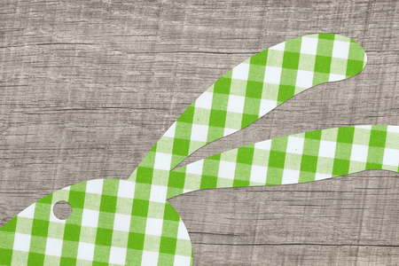 ear checked: Wooden easter background with an apple green checked bunny.