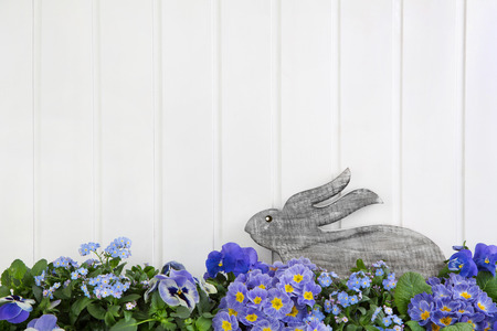 Easter bunny sitting in blue and purple spring flowers. Idea for a greeting card background in country style.