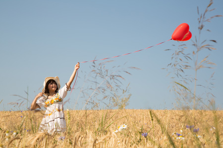 Romantic young woman walking in a wreath field holding a red heart balloon. Love concept with background.
