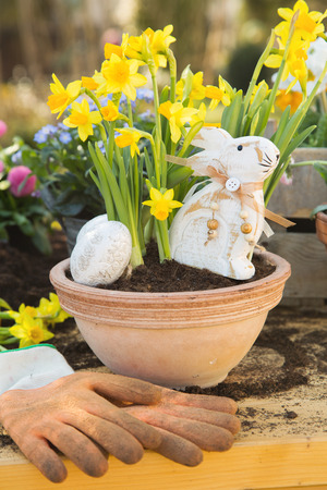 homelike: Easter handmade decoration with spring flowers and rabbits at home in the garden. Stock Photo