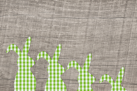 Wooden easter background with a apple green checked bunny family.