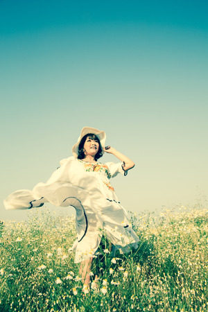 Happy smiling young girl wearing a country style dress with hat dancing in a flower field in summer.