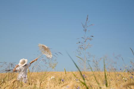 Espoir, rêves et futur concept avec fond de ciel bleu et un jeune womanl tenant un pied de parasol dans un champ de couronne.