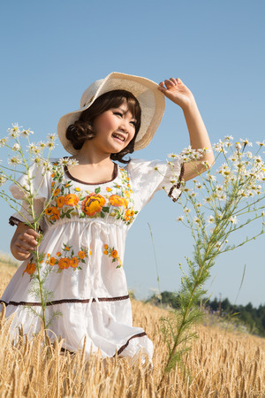 Bonne jeune fille asiatique en été face au soleil dans un champ de blé.
