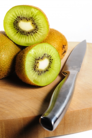 Fresh Kiwi Fruit on Chopping Board with a knife photo