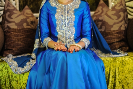 Bride Wearing a blue dress sitting on an altar, head not seen photo