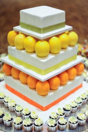 tier: Orange Lemon 3 tier white wedding cake with mini cupcakes