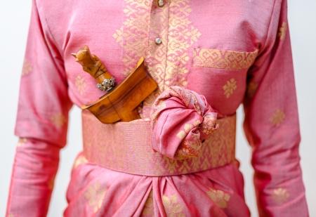 ピンクの伝統的なマレー ソンケットの結婚式の服装を着て新郎