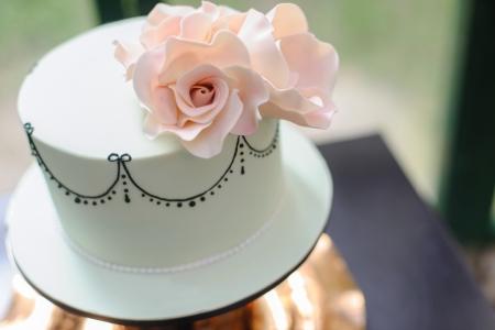 装飾としてピンクの花と白いフォンダン ケーキ