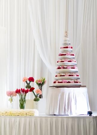 Multi Tier Big Wedding Cake decorated with fresh flowers Stock Photo