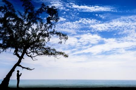 ビーチでツリーの下で祈っている人のシルエット